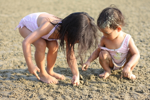 Zara showing Zaria how to dig for crabs