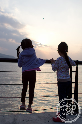 Girls throwing pebbles into Danshui River