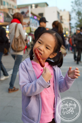 Zaria eating a Taiwan grilled sausage